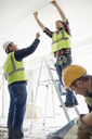 Construction worker on ladder at construction site - CAIF11634