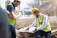 Construction worker and engineer reviewing blueprints at construction site - CAIF11637