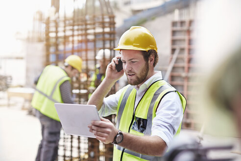 Engineer with digital tablet talking on cell phone at construction site - CAIF11640