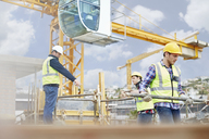 Foreman guiding construction workers below crane at construction site - CAIF11643