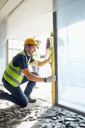 Construction worker using level tool at construction site - CAIF11652
