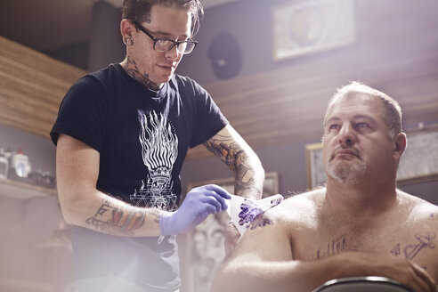 Tattoo artist tattooing man's shoulder - CAIF11664