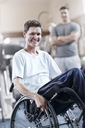 Portrait smiling man in wheelchair at physical therapy office - CAIF11667