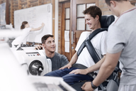Physical therapists guiding man at machinery - CAIF11682