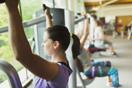 Focused woman using exercise equipment at gym - CAIF11700