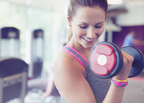 Close up smiling woman doing dumbbell biceps curls at gym - CAIF11703