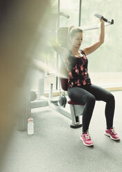 Woman using exercise equipment at gym - CAIF11709