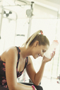 Tired woman cooling forehead with water bottle at gym - CAIF11712