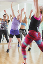 Women with arms raised in exercise class - CAIF11718