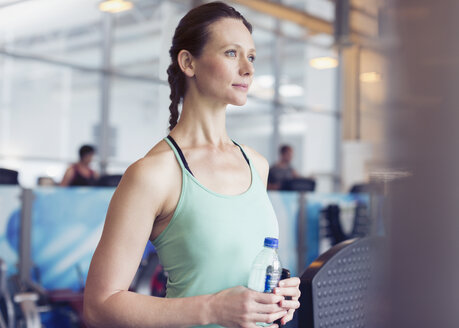 Pensive woman drinking water at gym - CAIF11721