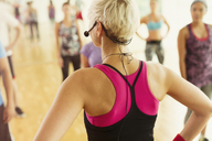 Rear view fitness instructor with headset leading aerobics class - CAIF11730