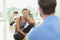 Smiling woman talking to man at gym - CAIF11748