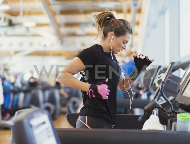 Woman running on treadmill at gym with headphones - CAIF11751