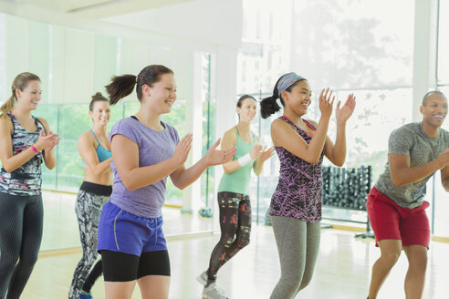 Smiling students clapping in aerobics class - CAIF11754