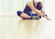 Woman stretching on gym studio floor - CAIF11757