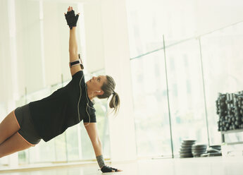 Woman balancing in side plank in gym studio - CAIF11763