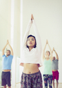 Serious woman with arms raised in yoga class - CAIF11766