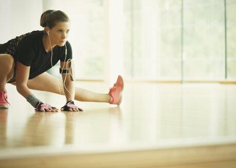 Focused woman stretching leg at gym studio mirror - CAIF11769