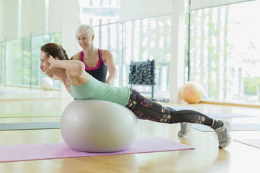 Personal trainer guiding woman doing back extensions on fitness ball - CAIF11781