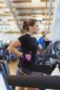 Focused woman running on treadmill at gym - CAIF11787