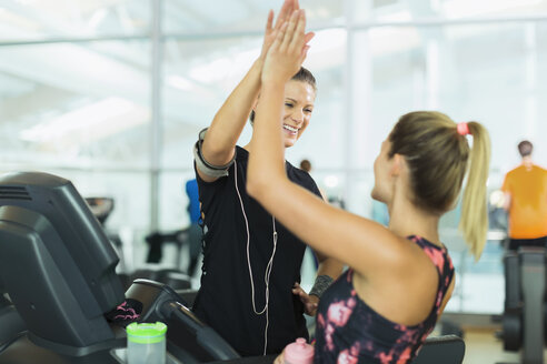 Smiling women high fiving at gym - CAIF11790