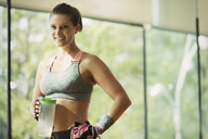 Portrait smiling woman holding water bottle at gym - CAIF11793
