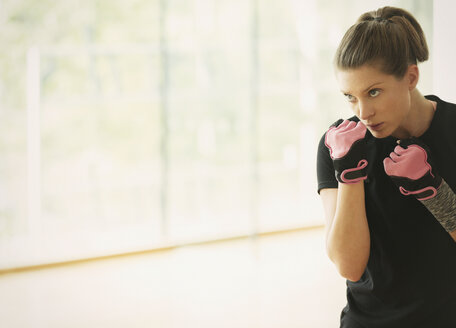 Focused woman shadow boxing in gym studio - CAIF11796