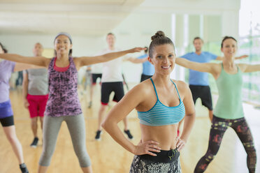 Portrait smiling fitness instructor leading aerobics class - CAIF11799