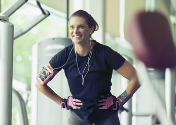 Smiling woman wearing headphones and mp3 player arm band stretching with hands on hips - CAIF11802