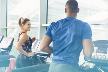 Man and woman jogging on treadmills at gym - CAIF11808