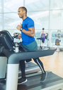 Man running on treadmill at gym - CAIF11811
