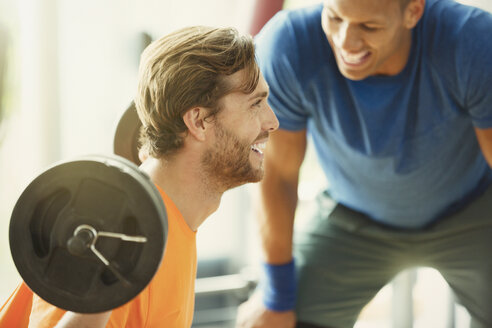Personal trainer encouraging man doing barbell squats at gym - CAIF11814