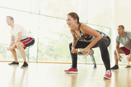 Smiling woman squatting in aerobics class - CAIF11817