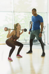 Personal trainer guiding woman doing barbell squats at gym - CAIF11823