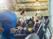 Smiling man running on treadmill at gym - CAIF11829