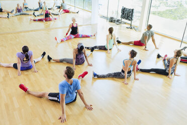 High angle view exercise class stretching with legs apart at gym - CAIF11835