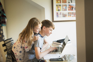 Sister watching brother using laptop in bedroom - CAIF11844