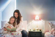 Mother and daughter reading book in bedroom - CAIF11850