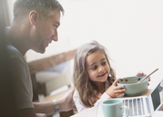 Father and daughter eating breakfast at laptop - CAIF11853