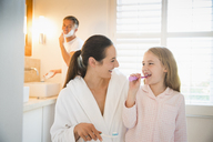 Mother and daughter brushing teeth in bathroom - CAIF11865