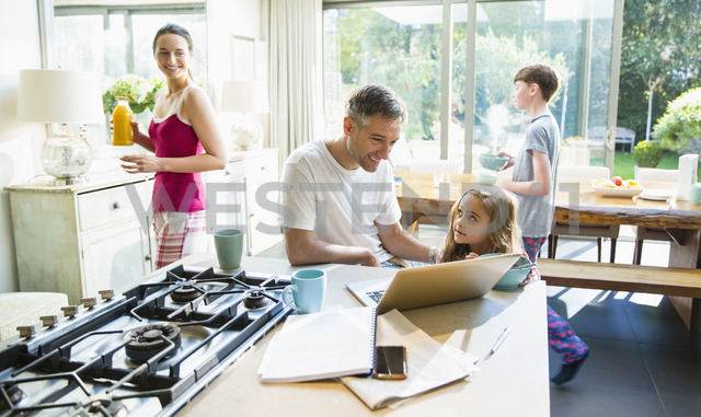Family with breakfast and laptop in morning kitchen - CAIF11883