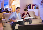 Father and son eating pizza and playing video game in living room - CAIF11889
