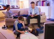 Family relaxing with technology in living room - CAIF11892