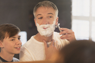 Son watching father shave face in bathroom mirror - CAIF11898