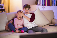 Brother covering surprised sister's eyes watching TV in living room - CAIF11901