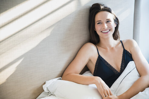 Smiling woman relaxing in morning bed - CAIF11904