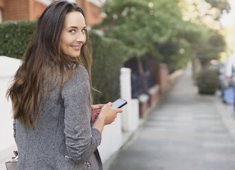 Portrait smiling businesswoman with cell phone looking back on sidewalk - CAIF11907