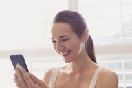 Smiling woman texting with cell phone at window - CAIF11910