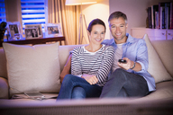 Smiling couple watching TV in living room - CAIF11913