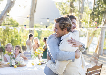 Bridegroom and best man embracing during wedding reception in domestic garden - CAIF11919
